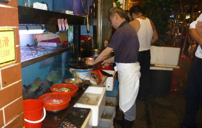 Seafood tanks and cooks at street food stalls